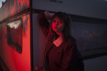 Portrait of confident young woman wearing jacket while standing by wall in red illuminated room
