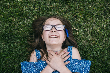 Overhead view of cheerful girl lying on grassy field at park