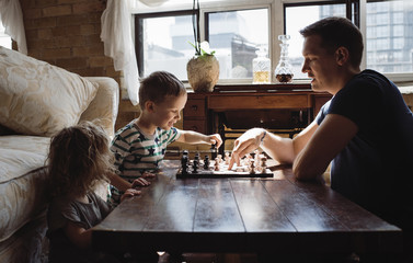 Side view of father playing chess with children on table at home