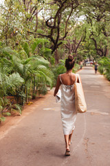 Back view of woman in white dress walking