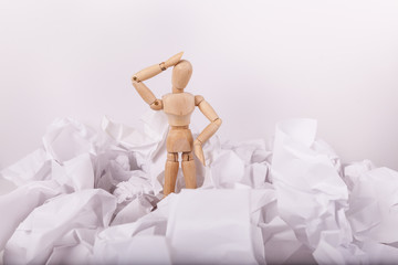 Wooden mannequin doll standing frustrated scratching head in piles of crumbled balls of white paper