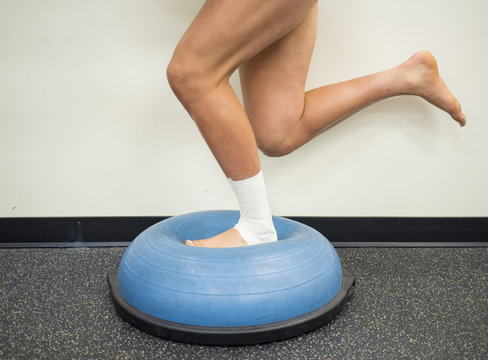 Athlete with a sprained ankle doing strengthening and balance exercises on a bosu ball
