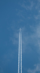 Airplane flying at high altitude leaving its white wake over blue sky