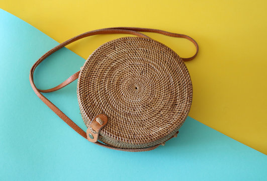 Handwoven Boho Bali Round Rattan Beach Bag With Button Clip on a yellow and turquoise background