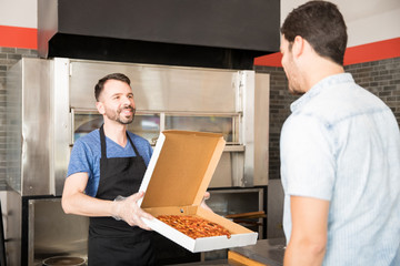 Foto auf Acrylglas Pizzeria Smiling chef holding pizza in box in front of customer
