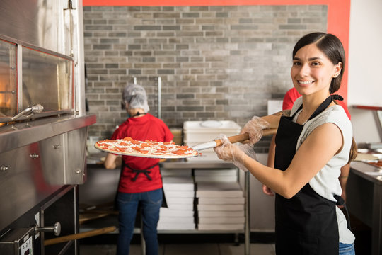 Pretty woman chef putting fresh made pizza in oven