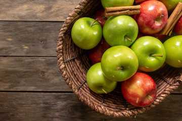 Apples red and green on rustic wooden table in basket