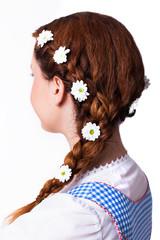 junge attraktive Frau im Dirndl  mit Blumen-Schmuck in geflochtenem Zopf