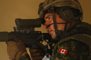 A Canadian soldier with the Royal 22e Regiment takse aim from his position as they conduct assault operations during a Rim of the Pacific (RIMPAC) exercise with U.S. Marines at Camp Pendleton