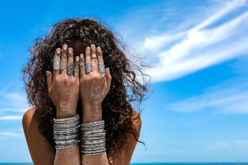beautiful young woman on the beach background cover her face with hands with silver bracelets and rings