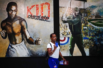 Wrestling athlete Yudari Sanchez takes a selfie next to images depicting Cuban late President Fidel Castro and late Cuban boxer Kid Chocolate at the Cuban Sports Hall after its inauguration in Havana