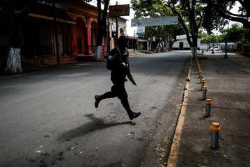 A riot police officer runs during clashes with anti-government protesters in the indigenous community of Monimbo in Masaya, Nicaragua