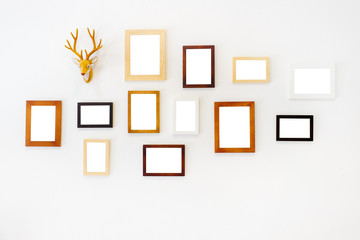 Blank wooden square photo frame modern interior design decorated with rain deer cartoon model on white wall background with copy space for text or image.