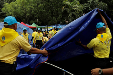 "Volunteers remove tents as they clear the campsite of the rescue mission for the 12 boys of the ""Wild Boars"" soccer team and their coach, near the Tham Luang cave complex, in the northern province of Chiang Rai"