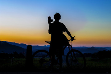 Silhouette of photographer in action take photo with bike on mountain with sunrise.