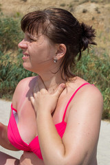 woman holds her neck on the beach
