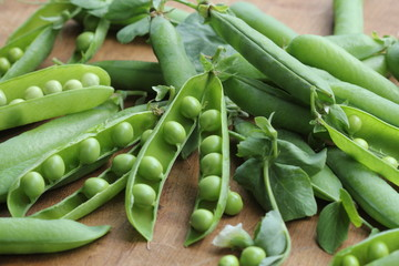 Ripe pods of green peas, fresh green peas on wooden table, close up