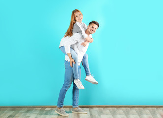 Young couple in stylish jeans near color wall