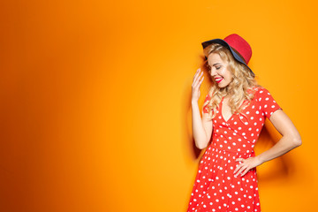 Stylish young woman with hat posing on color background