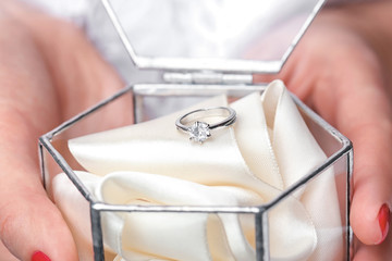 Woman holding glass box with beautiful engagement ring, closeup
