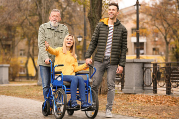 Woman in wheelchair with her family outdoors on autumn day