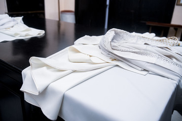 The white cassock of the priest lies on the table
