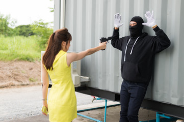 A woman pointing a gun to a villain who wear black mask and black clothes. The villain raised both hands to show his surrender.