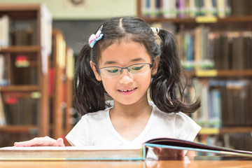 School education and literacy concept with Asian girl kid student learning and reading book in library or classroom