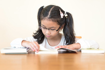 School education and literacy concept with Asian girl kid student learning hard and reading book in library or classroom