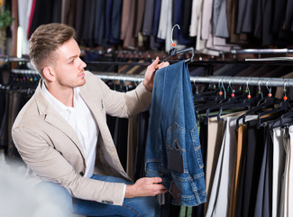 male customer examining trousers in men's cloths store