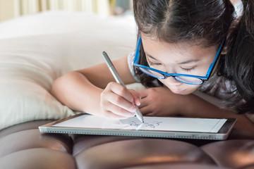 Asian school child girl using smart  tablet device digital technology drawing on innovative...