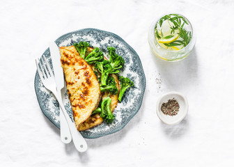Omelet with broccoli and tarragon lemon lemonade on a light background, top view. Healthy breakfast or snack. Flat lay