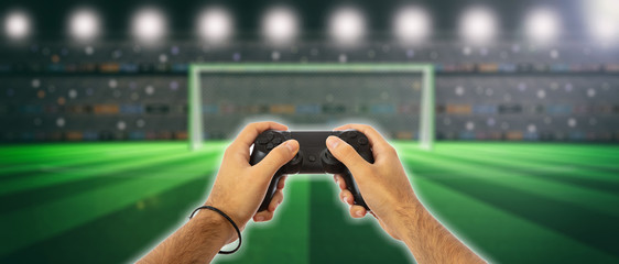 Male hands holding a video game controller on blur screen background