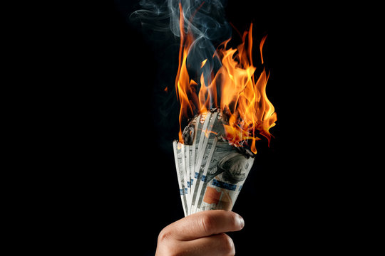 Male hand close-up, holds burning money in hands, burning US dollars. Black background, isolate. The concept of inflation, a decrease in the purchase of foreign currency, and devolution.