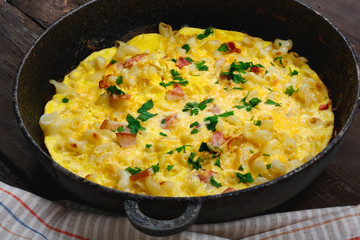 Traditional rustic omelette with bacon, pasta and greens