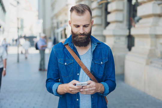 Man standing texting on a mobile on a city street