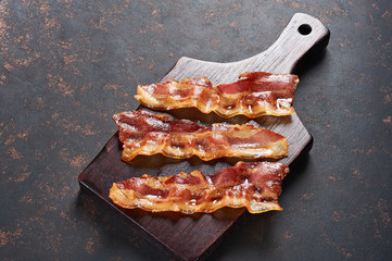 Fried bacon on wooden cutting board. Top view, isolated on black background.