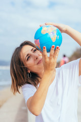 Woman holding a geographic globe on the beach