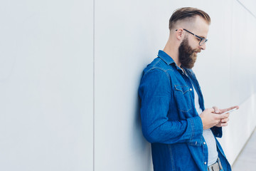 Relaxed bearded man using a mobile phone