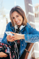 Smiling woman relaxing with a smartphone and music