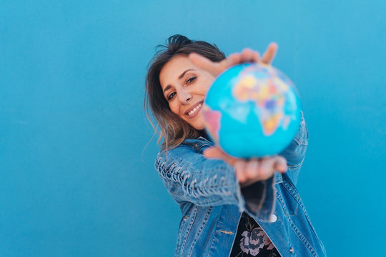 Smiling woman holding a globe in her hands