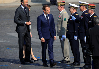 French President Emmanuel Macron and Prime Minister Edouard Philippe arrive to attend the traditional Bastille Day military parade on the Champs-Elysees Avenue in Paris