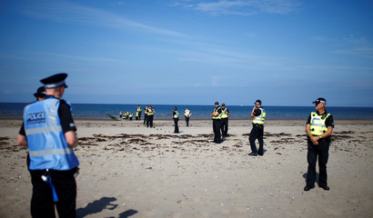 Police officers form a barrier on the beach near the golf resort owned by U.S. President Donald Trump, during Trump's stay at the resort, in Turnberry