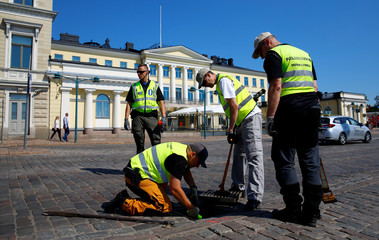 A police officer and members of the defense forces check a manhole in front of the Presidential Palace in Helsinki