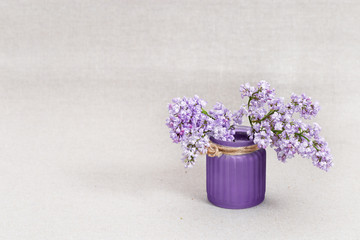Vase with lilac flowers on cloth background with copy space. Minimal concept.