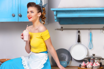 Retro / pin up girl woman female housewife wearing colorful top, skirt and white apron holding sweet strawberry milkshake sitting on the cabinet in the kitchen with utensils and tray with cupcakes.