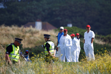 Caddies and golfers look at police officers in the grounds of the golf resort owned by U.S. President Donald Trump, during Trump's stay at the resort, in Turnberry