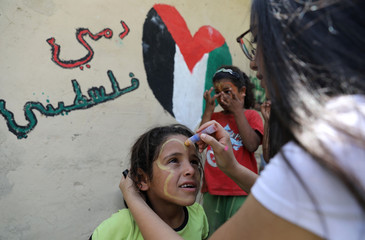 A girl gets her face painted during the visit of Palestinian Prime Minister Rami Hamdallah to the Bedouin village of Khan al-Ahmar that Israel plans to demolish, in the occupied West Bank