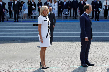 French President Emmanuel Macron, his wife Brigitte Macron and French Prime Minister Edouard Philippe leave after the traditional Bastille Day military parade on the Champs-Elysees avenue in Paris
