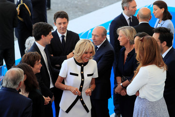 Brigitte Macron, wife of French President Emmanuel Macron, talks with members of the French government as she arrives to attend the traditional Bastille Day military parade on the Champs-Elysees Avenue in Paris